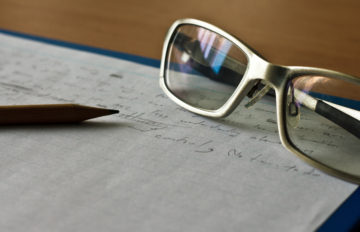 pencil, notebook and glasses in composition in sepia tone